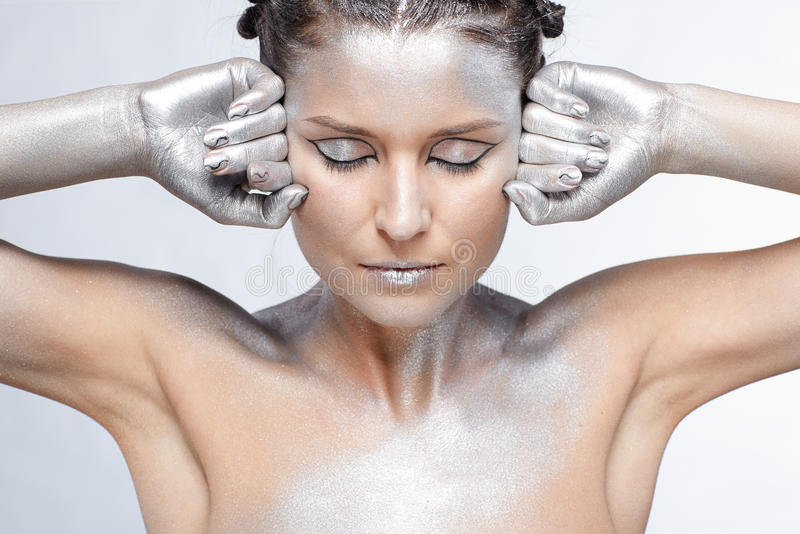 Silver girl. Portrait of girl body painted with silver posing on gray royalty free stock photos