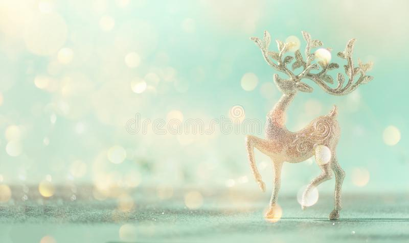 Silver glitter Christmas deer on blue background with lights bokeh, copy space. Greeting card for new year party. Festive holiday royalty free stock photo
