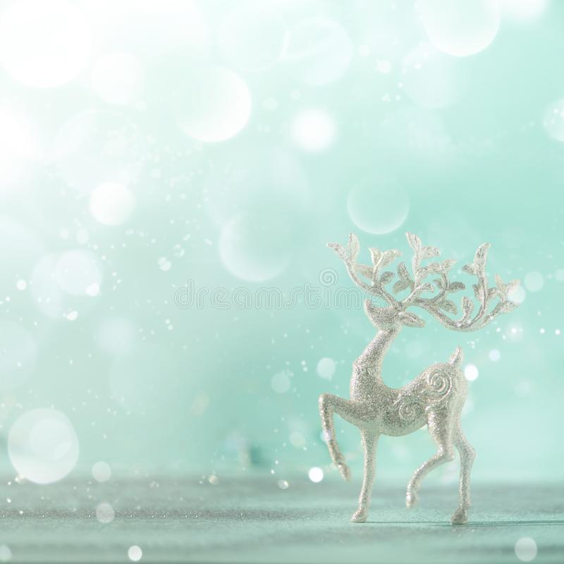 Silver glitter Christmas deer on blue background with lights bokeh, copy space. Greeting card for new year party. Festive holiday royalty free stock photography