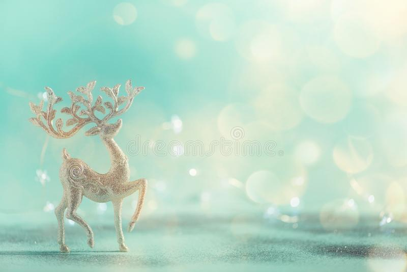 Silver glitter Christmas deer on blue background with lights bokeh, copy space. Greeting card for new year party. Festive holiday royalty free stock images