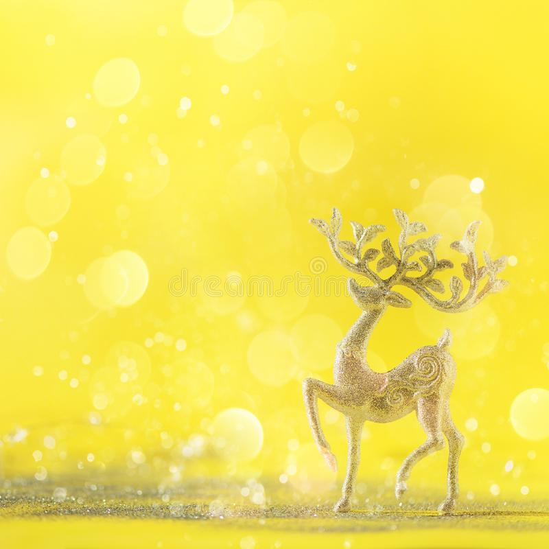 Silver glitter Christmas deer on yellow background with lights bokeh, copy space. Greeting card for new year party. Festive stock photos