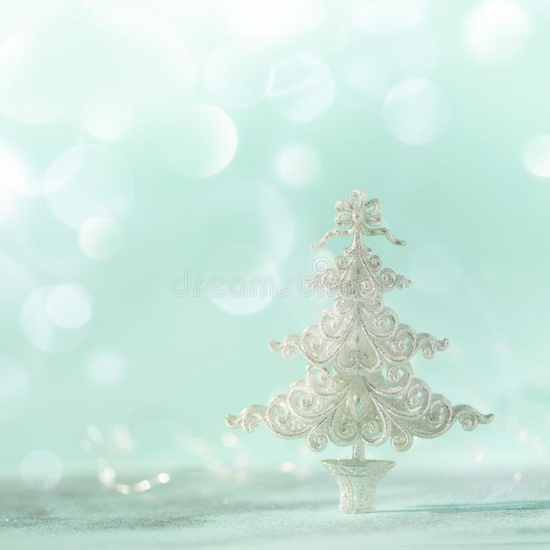 Silver glitter Christmas tree on blue background with lights bokeh, copy space. Greeting card for new year party. Festive holiday stock images