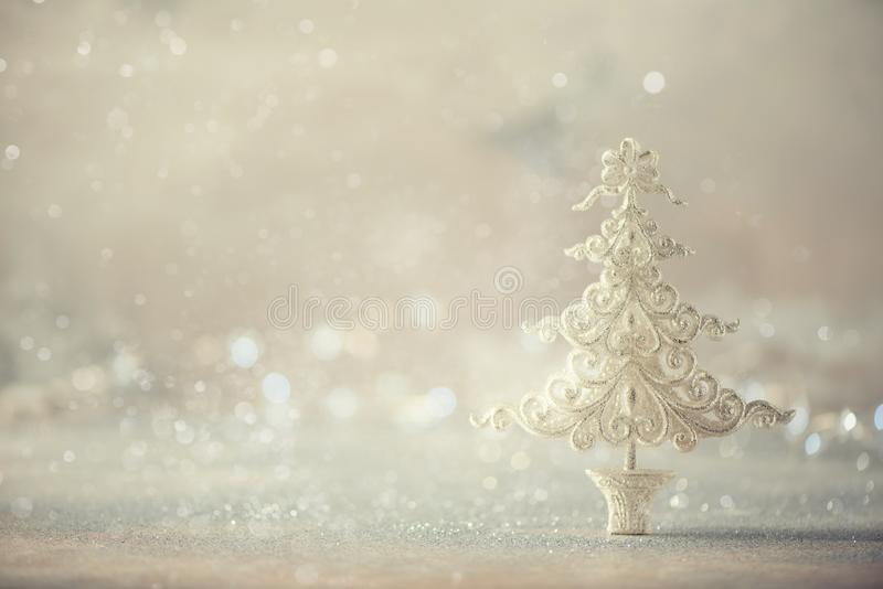 Silver glitter Christmas tree on grey background with lights bokeh, copy space. Greeting card for new year party. Festive holiday stock images