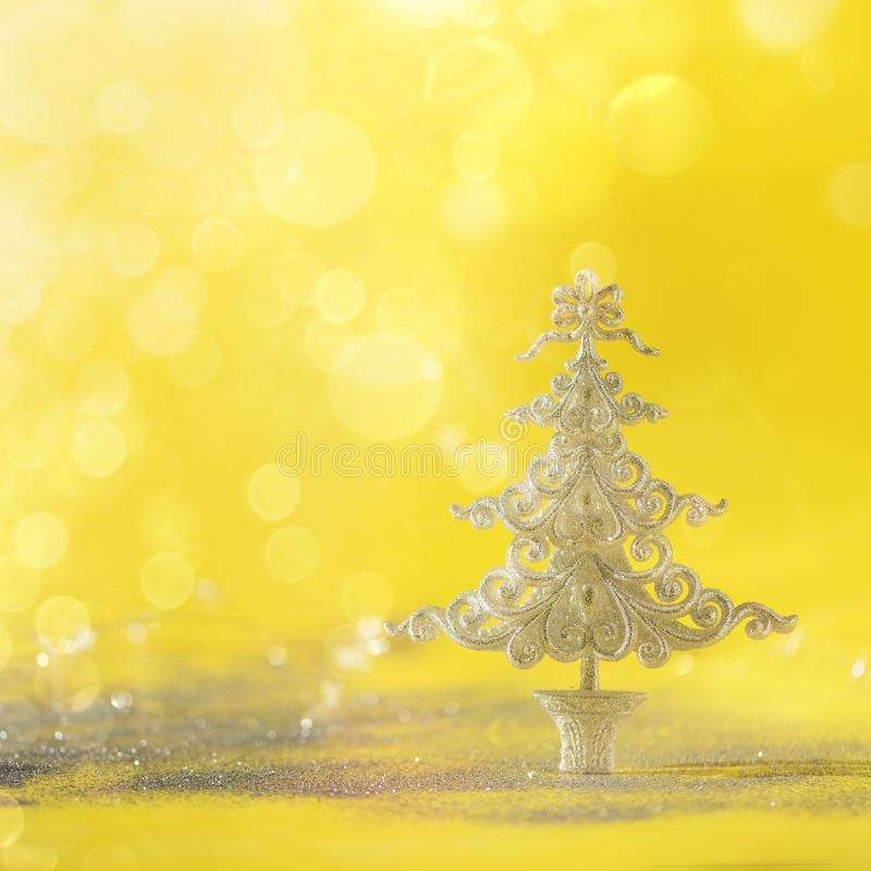 Silver glitter Christmas tree on yellow background with lights bokeh, copy space. Greeting card for new year party. Festive stock photos