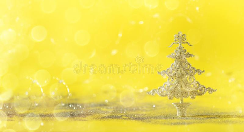Silver glitter Christmas tree on yellow background with lights bokeh, copy space. Greeting card for new year party. Festive royalty free stock photography