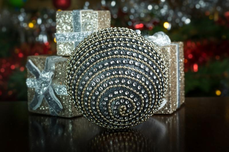 Silver globe decoration surrounded by gift boxes stock images