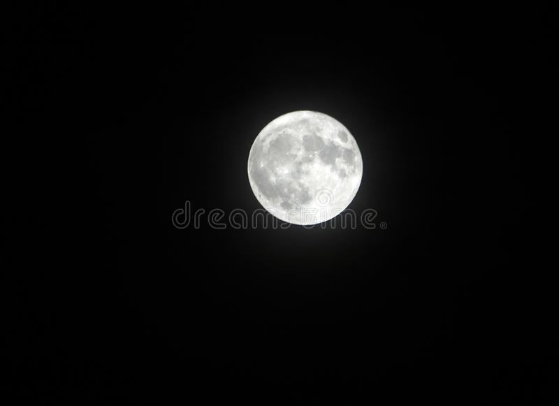 Silver glowing bright december full moon in a black sky royalty free stock photo