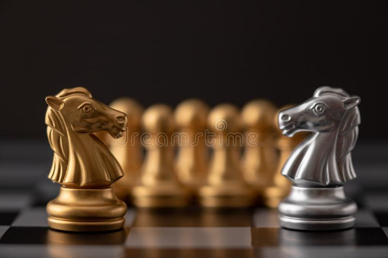 Silver and gold horse. Of the chess in the game on board, battle, bishop, business, castle, challenge, chessboard, choose, competition, concept, conflict royalty free stock photography