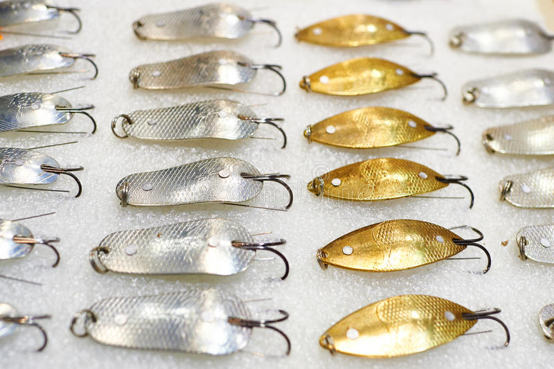 Silver and golden metal fishing lure stock photo