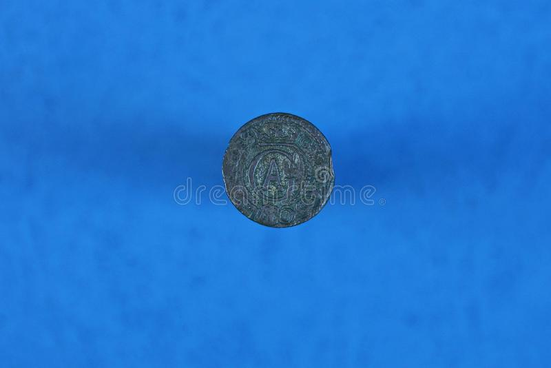 silver gray coin of lithuania on blue background stock photo