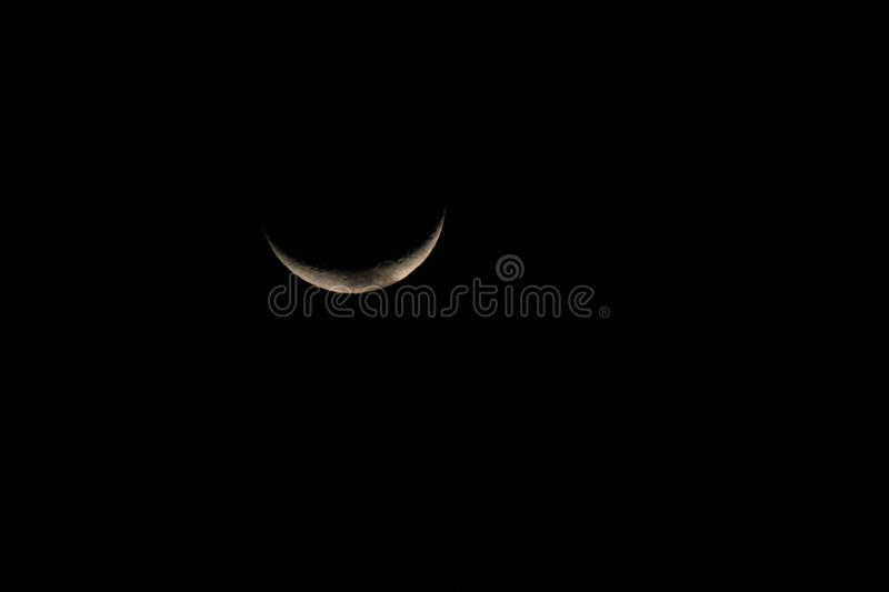 Silver half moon in a starless sky. Sliver of a silver crescent moon surrounded by the dark abyss of night as seen from earth stock photography