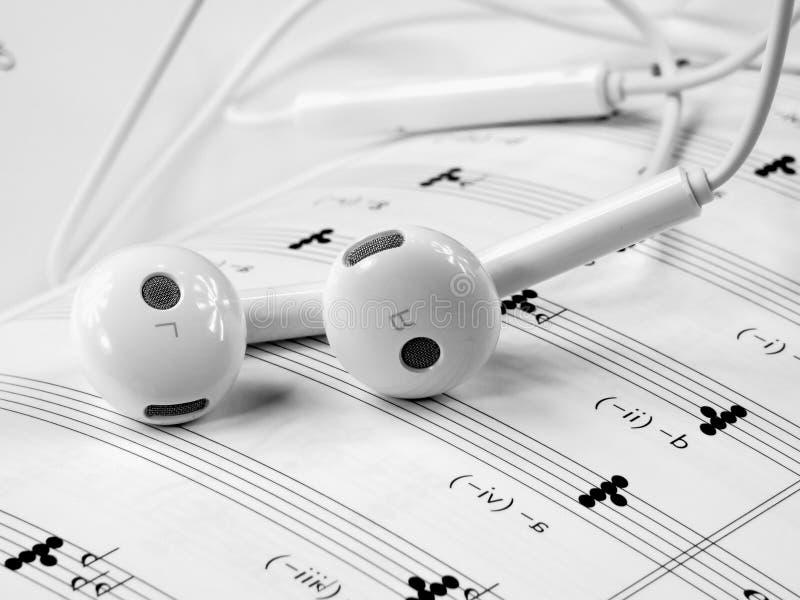 White headphones on sheet music royalty free stock photography