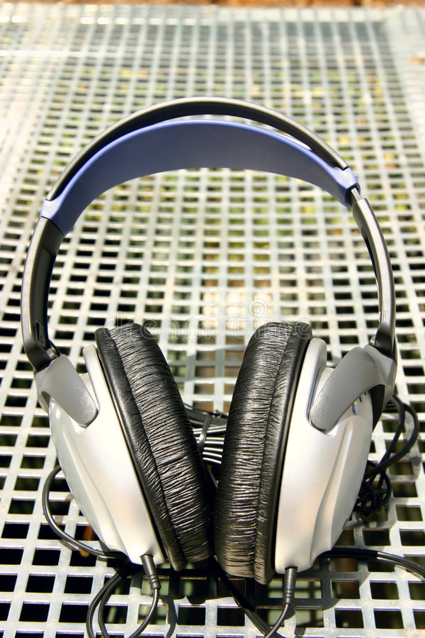 Silver headphones on silver grid background royalty free stock images