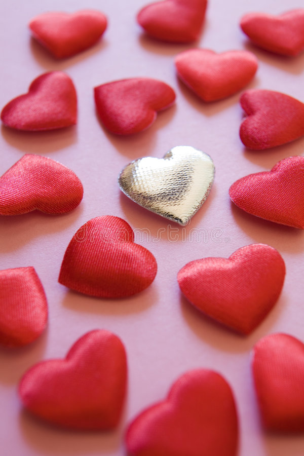 Silver heart amongst red hearts. On pink background royalty free stock images