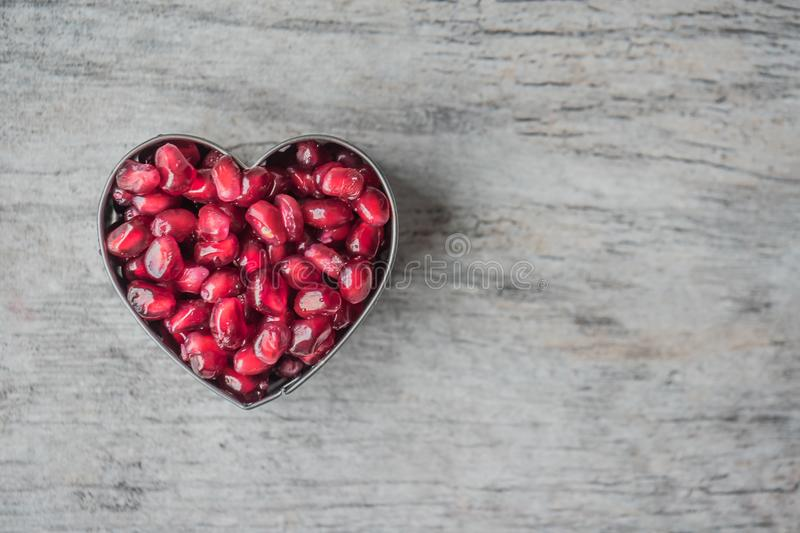 Silver Heart Bowl Filled of Red Pomegranate Seeds stock image