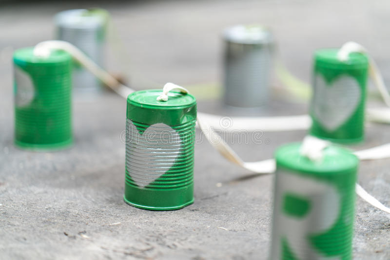 Silver heart on green cans connected with rope on cement floor. Cans attached with big bike for bride and groom riding together for new chapter of life. Just royalty free stock photo