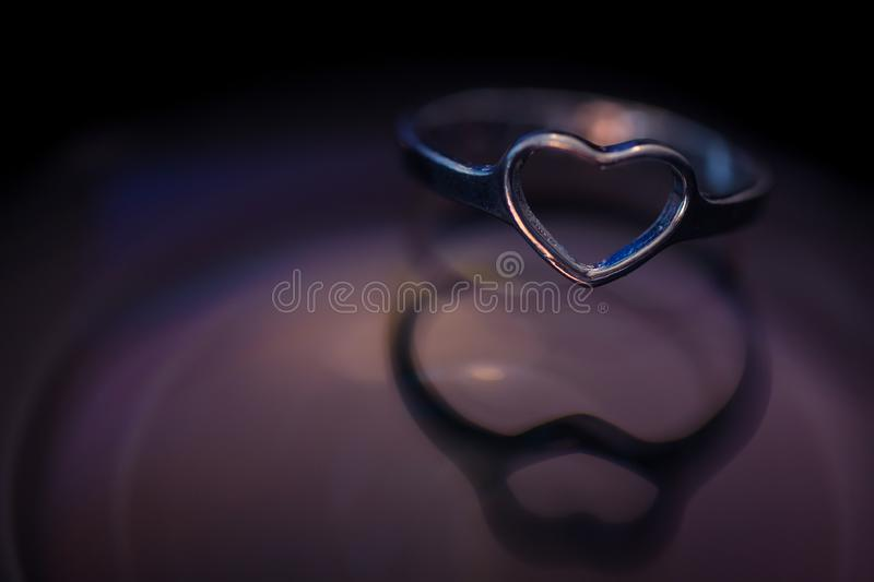 Silver heart shape ring with black and purple background.  stock photography