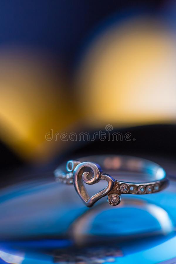 Silver heart shape ring with blue and yellow background.  royalty free stock photo