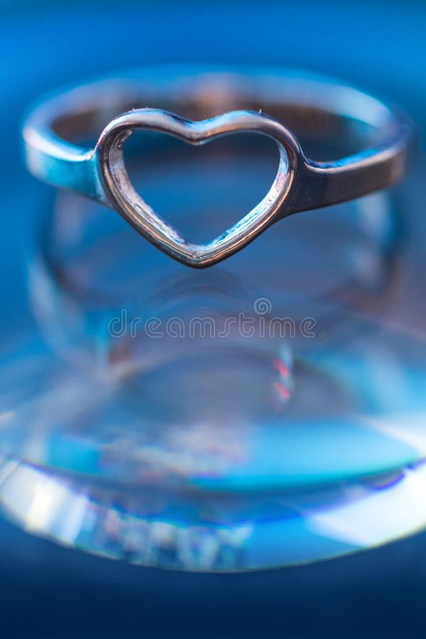 Silver heart shape ring with light blue background.  stock photos