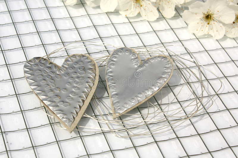 Silver hearts. A pair of silver hearts as a decoration royalty free stock photos