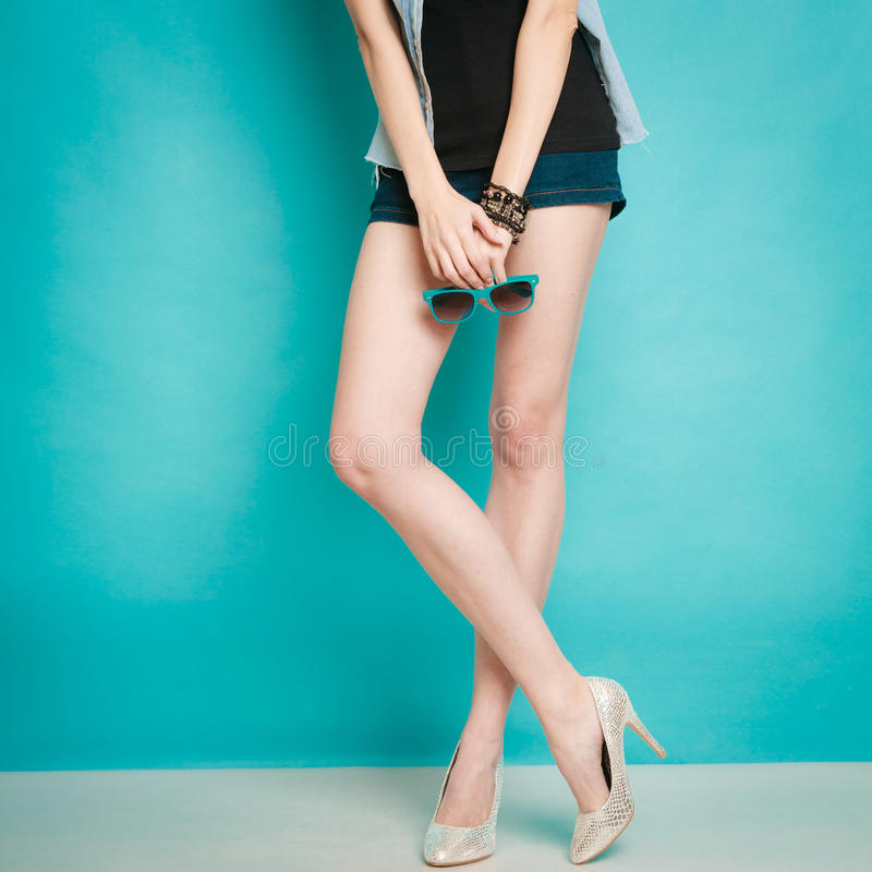 Silver high heels fashionable shoes on female legs royalty free stock photography