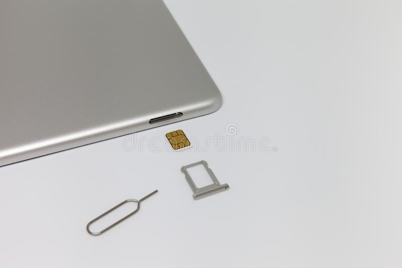 Silver inverted tablet. The SIM card tray is open. royalty free stock images