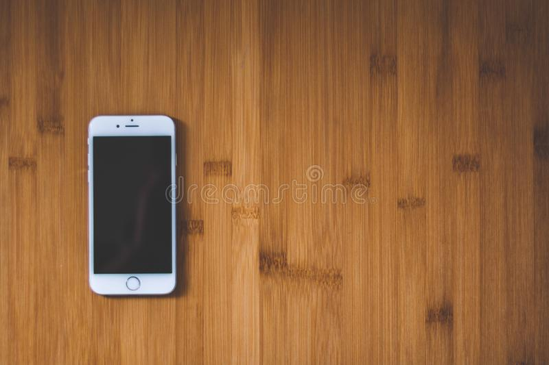 Silver Iphone 6 on Brown Wooden Surface royalty free stock photo