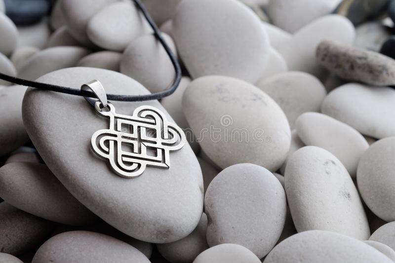 Silver jewelry with Celtic designs. For the neck on a leather rope lying on a sea white pebble royalty free stock photography
