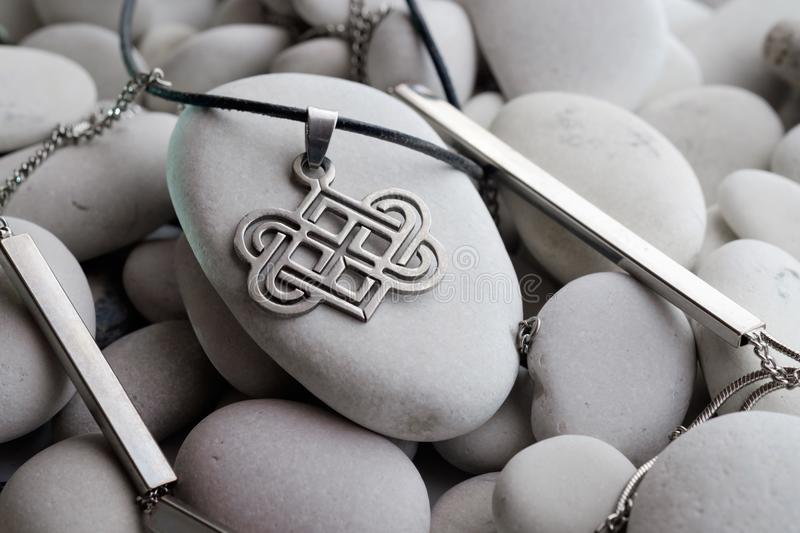 Silver jewelry with Celtic designs. For the neck on a leather rope lying on a sea white pebble royalty free stock photo