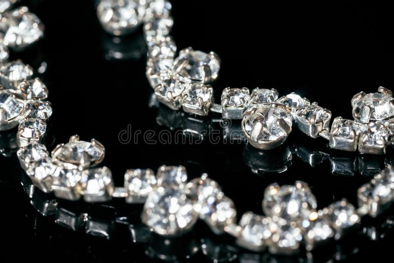 Silver jewelry with diamonds on a black background royalty free stock photography