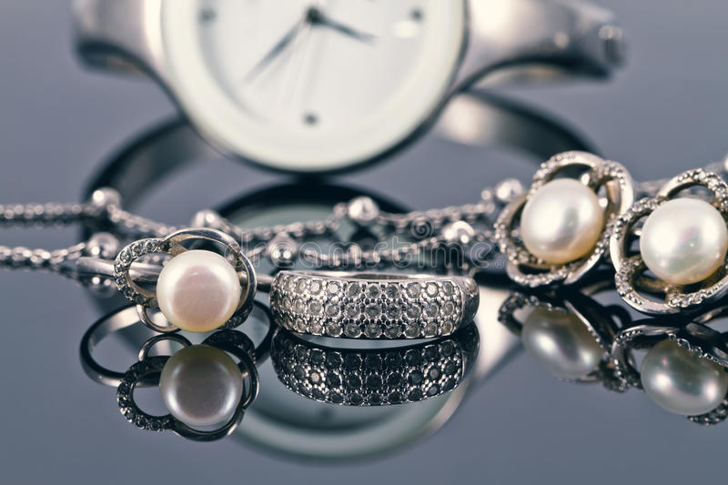 Silver jewelry with pearls and elegant women's watches stock images