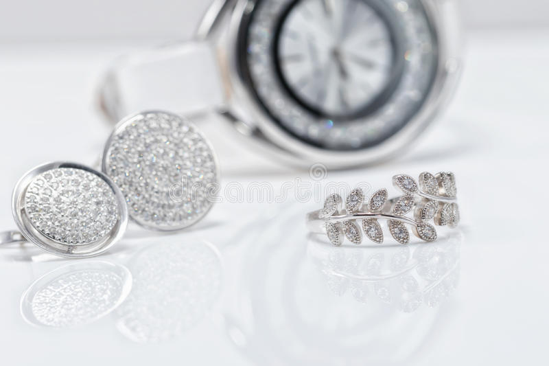 Silver jewelry with pearls and elegant women`s watches royalty free stock images