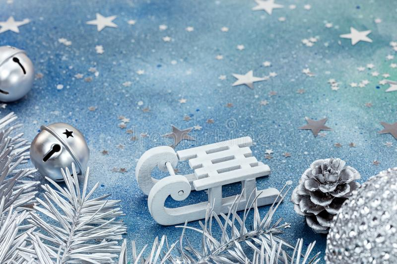 Silver jingle bells and christmas tree branches with white sledge on blue background. Silver jingle bells and christmas tree branches with white sledge on stock images