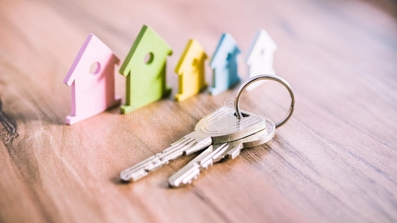 Silver Keychain in front of colourful miniature symbol of houses laying on the wooden surface stock images