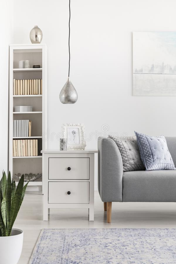 Silver lamp above cabinet next to grey sofa in white living room interior with bookshelf. Real photo royalty free stock photo