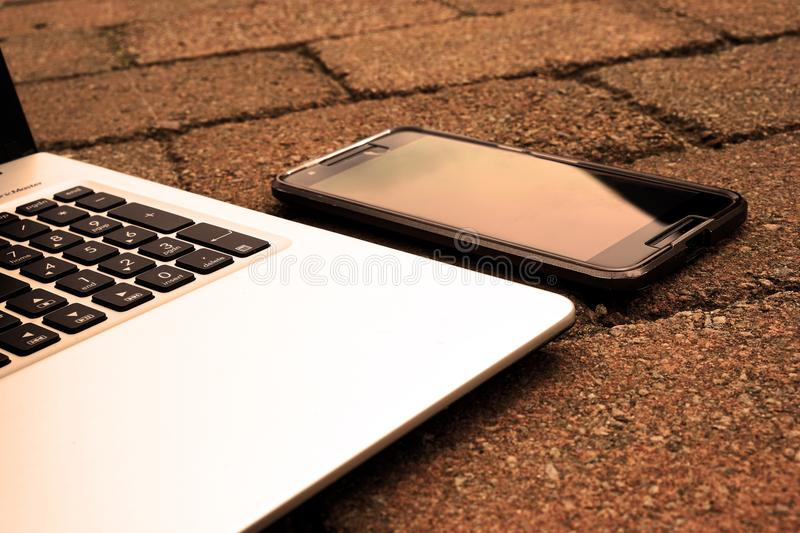 Silver Laptop Computer Beside Black Android Smartphone Turned Off royalty free stock photos