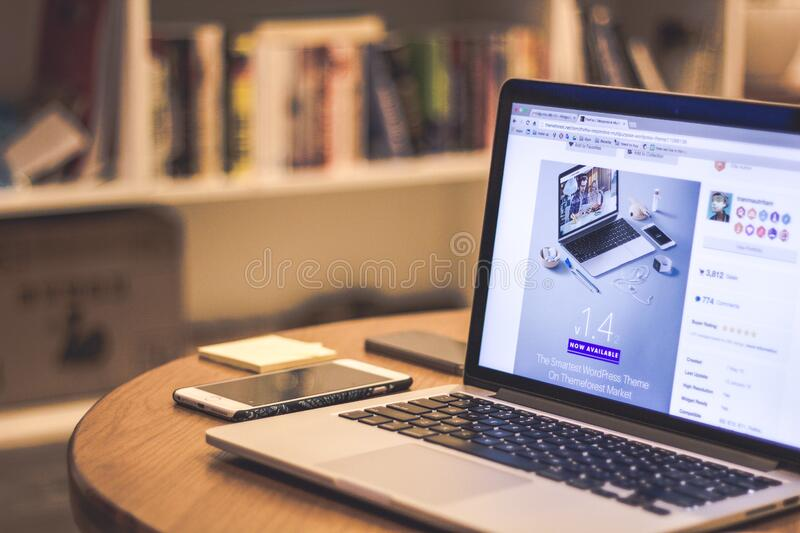 Silver Laptop Computer Beside White Smartphone on Brown Wooden Table stock photos