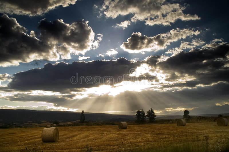 Silver-lined clouds over field. A dramatic scene of the sun shining from behind large clouds to produce a silver-lining effect. Under the sky, bales of hay sit stock photos