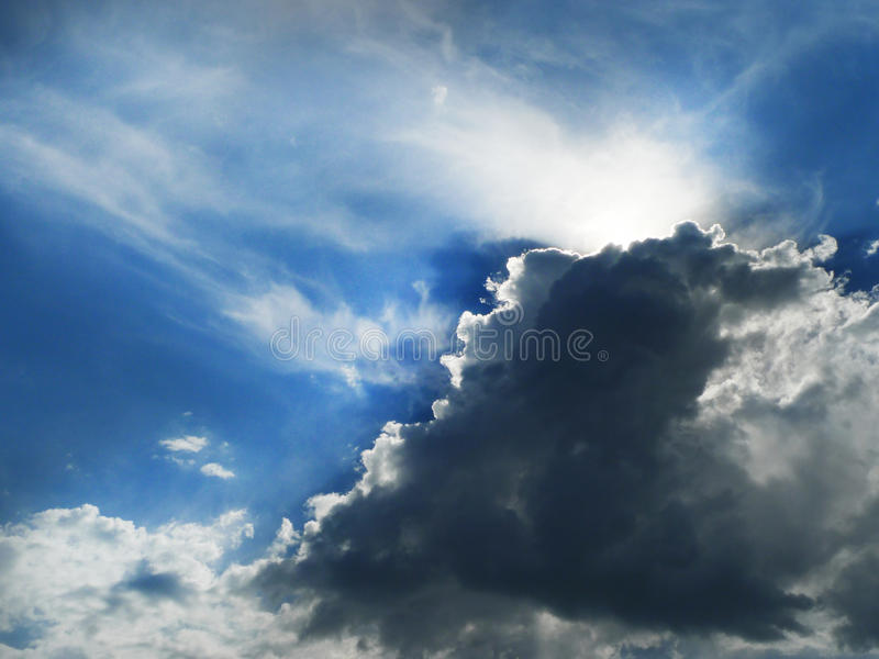 Silver lining with sunbeams, rising storm clouds stock image