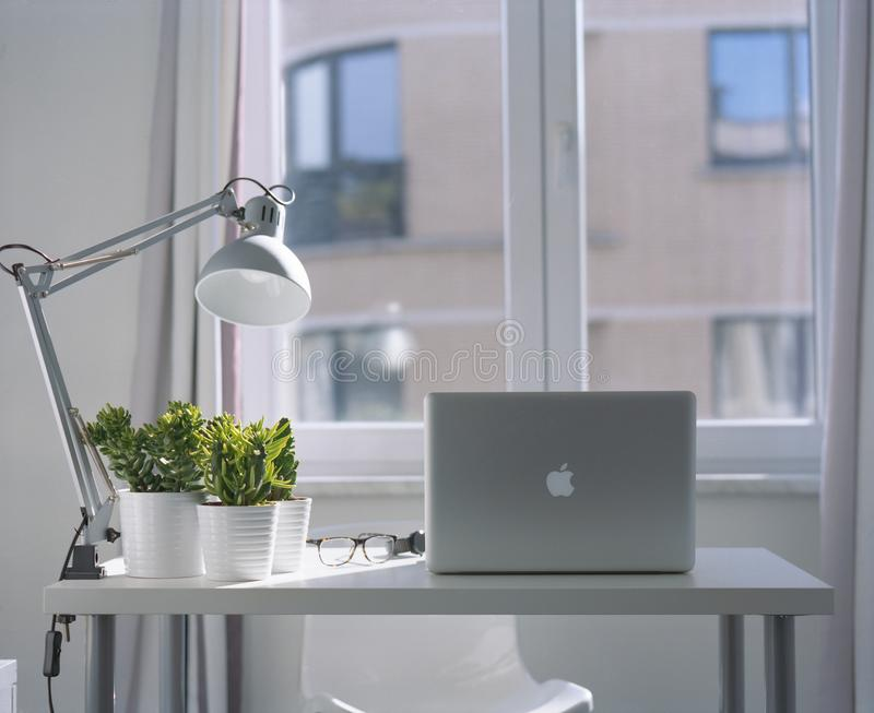 Silver Macbook Air and Goose Neck Lamp royalty free stock photos