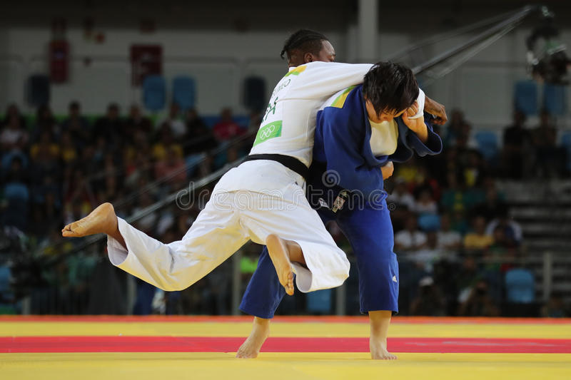 Silver medalist Judoka Audrey Tcheumeo of France in white in action against Sol Kyong of North Korea during women`s 78 kg match stock photography
