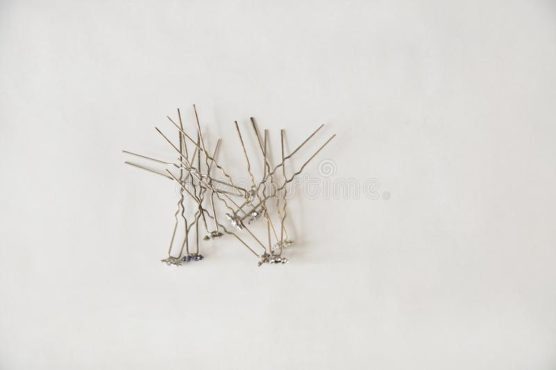 Silver metal hairpins with decorated flowers at the ends for hair lie in a random order on a white background. On the left side royalty free stock images