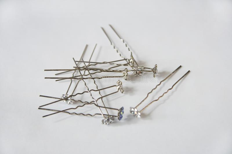 Silver metal hairpins with decorated flowers at the ends for hair lie in a random order on a white. Background horizontally stock images