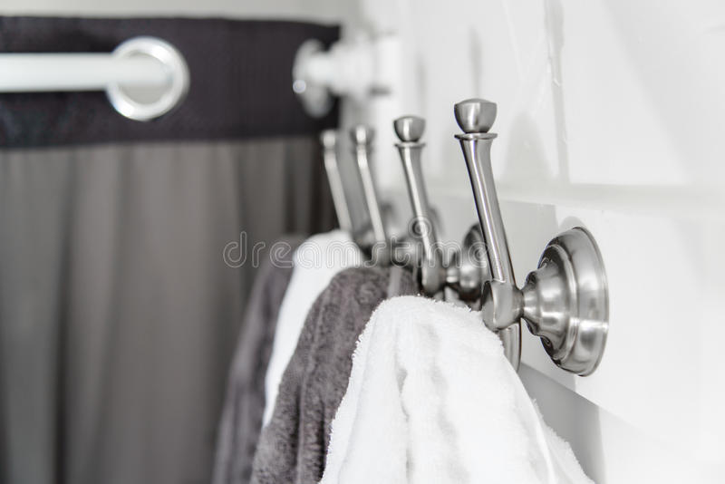 Silver Metal Hooks with White and Grey Towels stock image