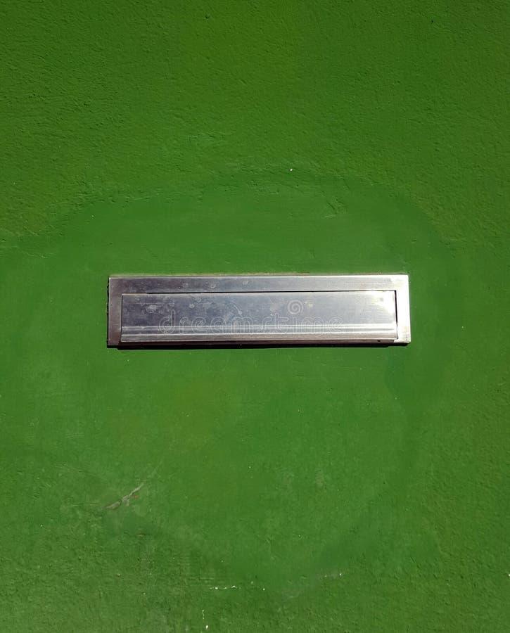 Silver metal letter box set into a vivid green concrete wall stock image