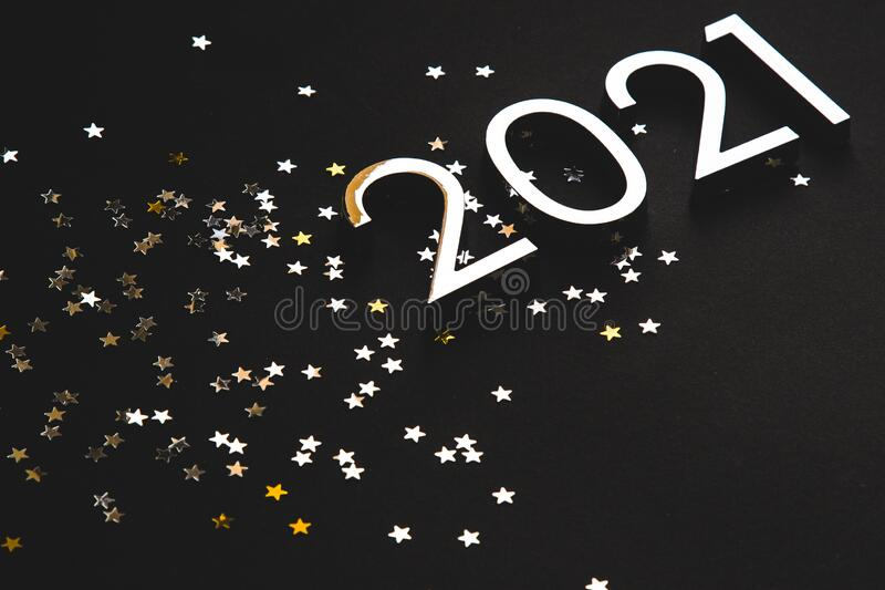 Silver metal numbers 2021 and stars on black background royalty free stock photo
