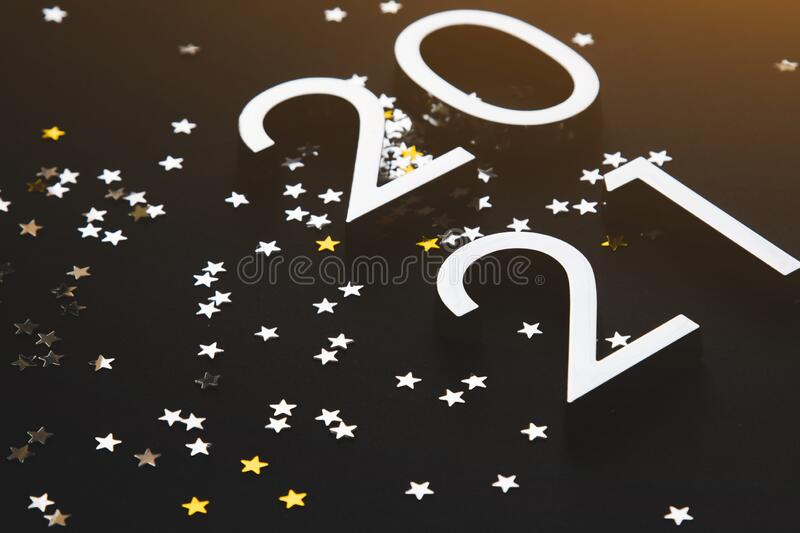Silver metal numbers 2021 and stars on black background royalty free stock photos
