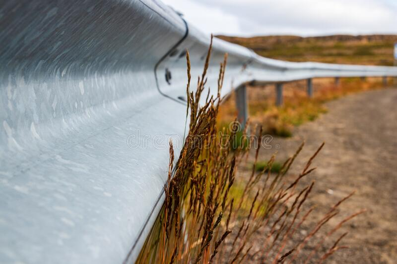 Metal Safety Guardrail Along The Road With Tall Grass And Weeds Growing. A silver metal safety auto guardrail along the side of a road where tall grass and weeds royalty free stock image
