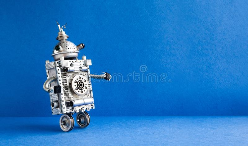 Silver metallic robot on blue background. Two wheels domestic servant robotic character with antenna. Creative design. Steampunk toy, copy space stock photography