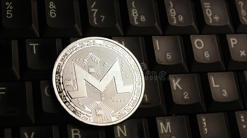 Silver Monero XMR coin on laptop keyboard royalty free stock images